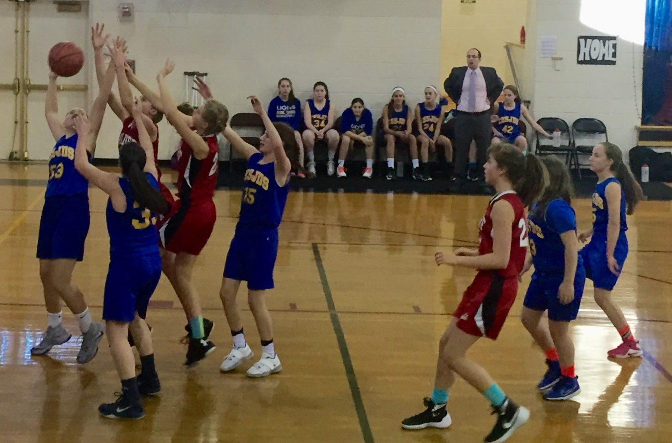 The Lions, along with the Washington Waldorf Knights, fight for the rebound at the Potomac Valley Athletic Conference championship. The Lions fell to the Knights with a final score of 32-17.