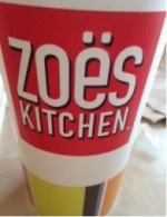 A cup from Zoes Kitchen which exhibits the color scheme of the restaurant.