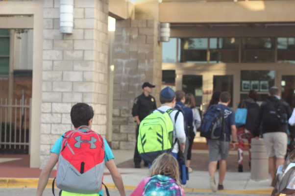 A Montgomery County policeman stands by the door and monitors the building as students enter the Upper School in the morning.