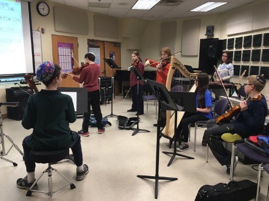 Middle school students practice scales at their strings sectional class.