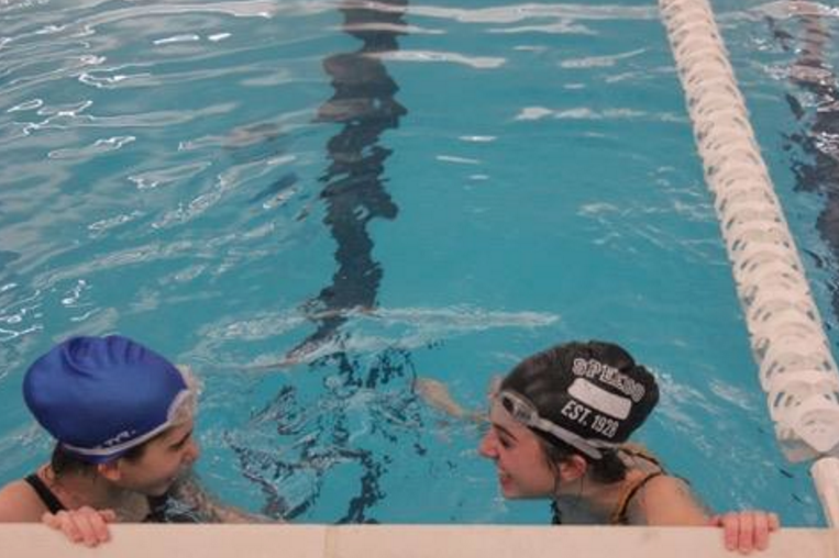 Sophomores Alexis Bell and Shira Finke rest on the wall during swim practice.
