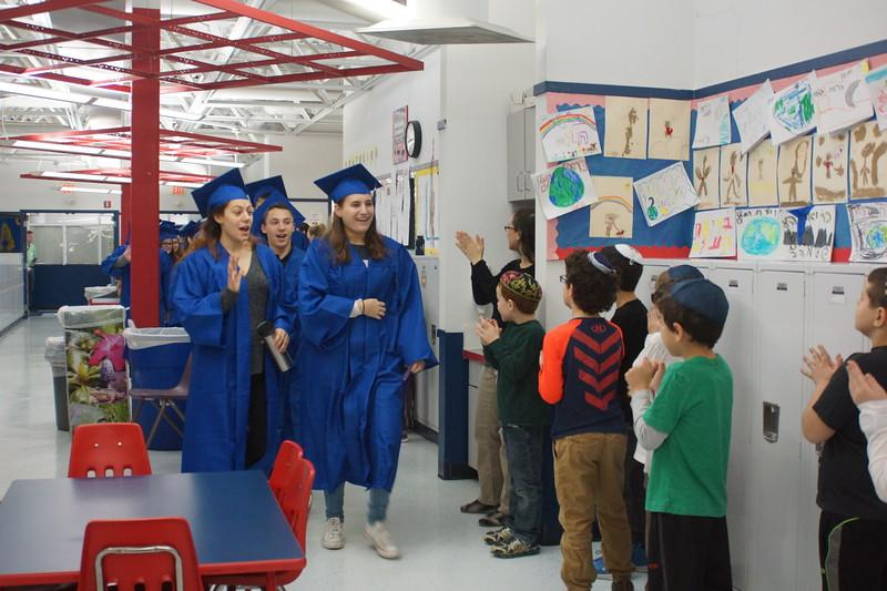 The Class of 2017 walks through the Lower School hallway as students look on and cheer.