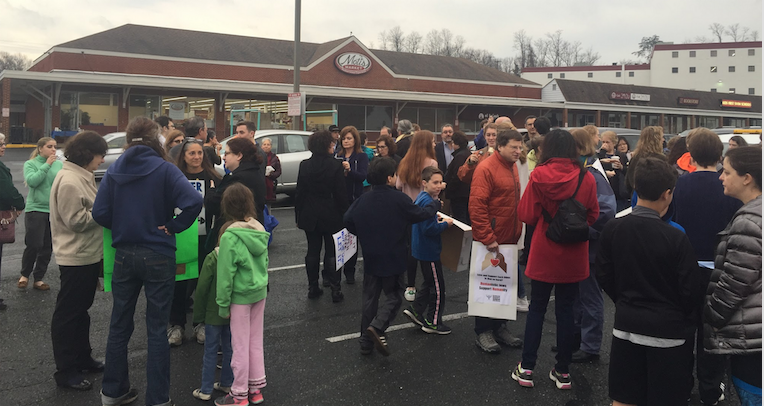 Community members talk and eat bagels outside of Moti's Market at a rally in support of the Jewish community and against recent anti-Semitism.