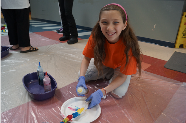 Sixth-grader+Tory+Boles+takes+a+break+from+painting+to+pose+for+a+picture+during+the+2016+Families+in+Action+Day.