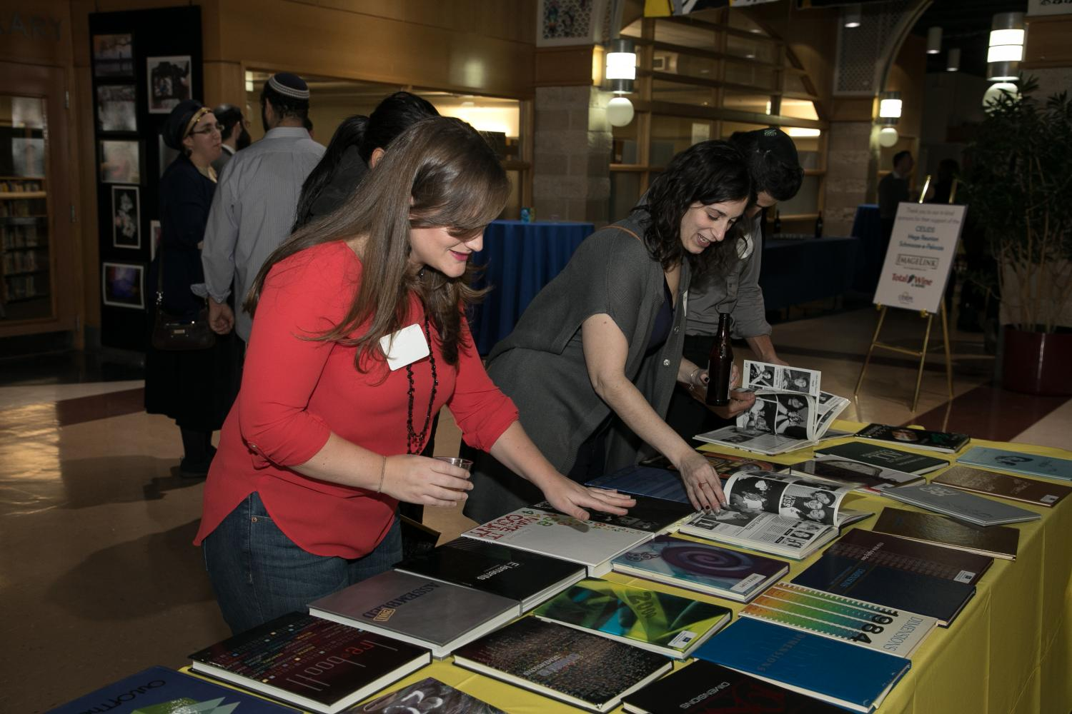 Alumni+browse+old+yearbooks+at+the+Upper+School+campus+at+a+February+reunion.