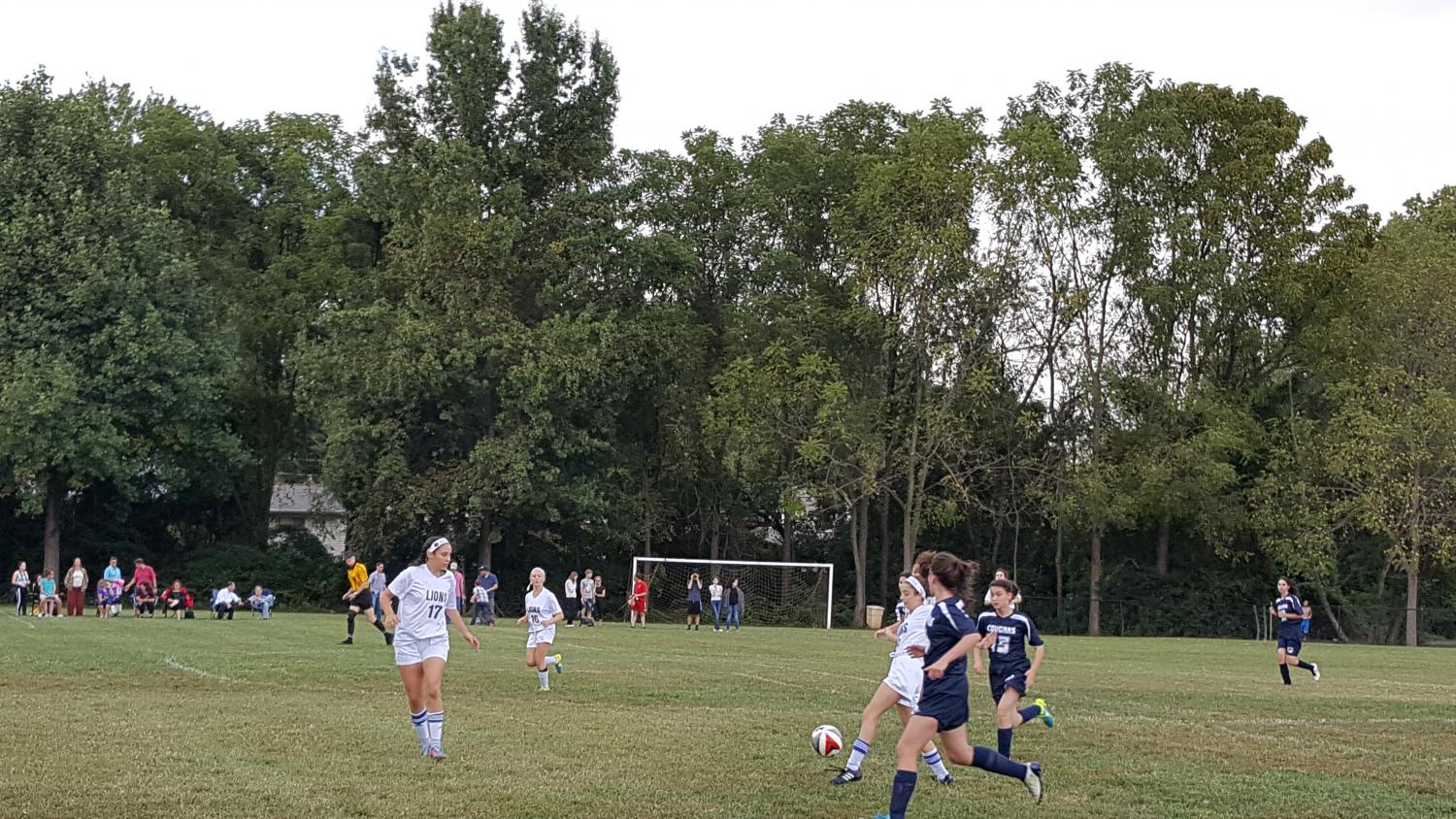 The Lions move the ball down the field, towards the opposing goal. The Lions beat the Berman Cougars 5-1 on the Lions' home field.