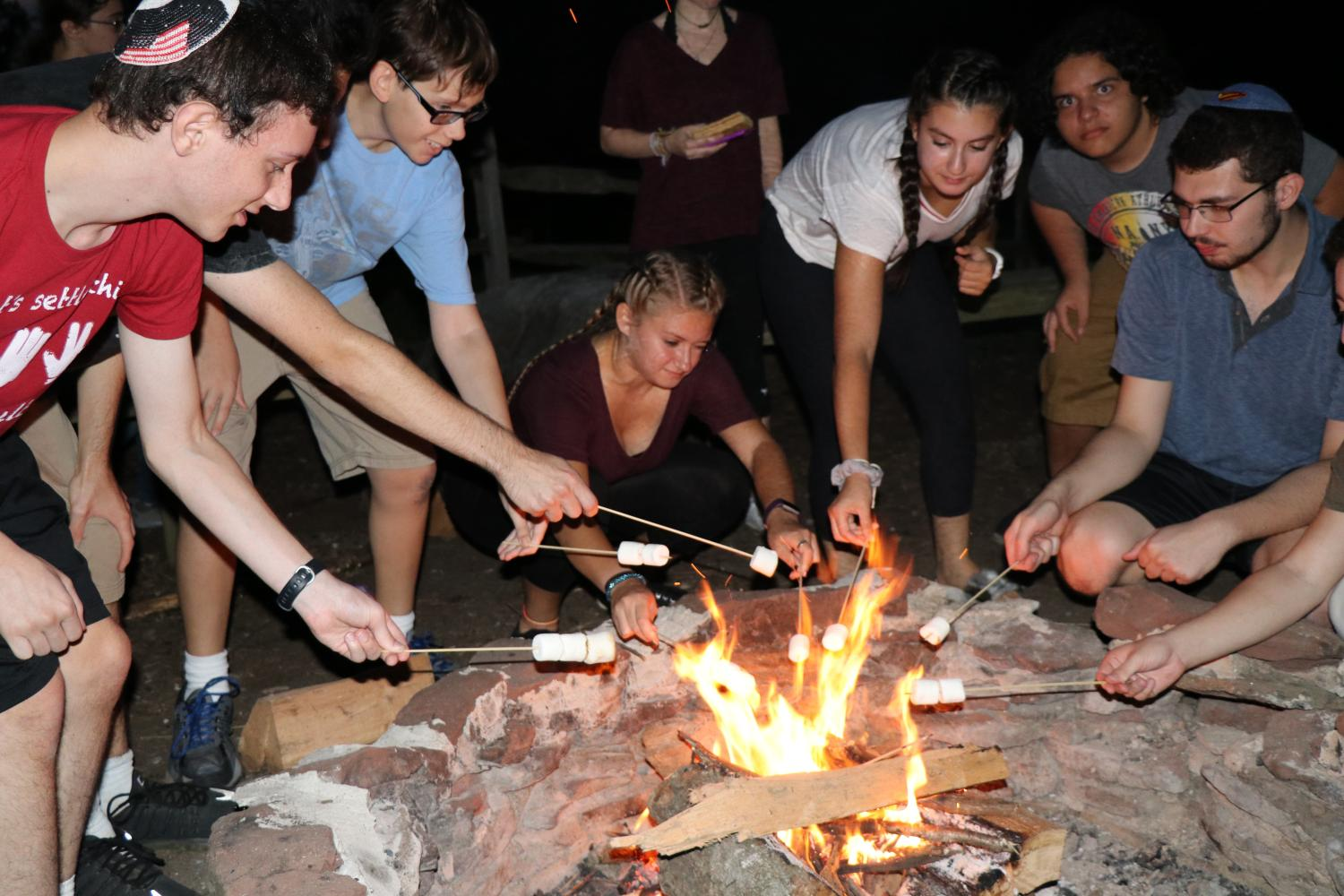 Senior gather around the campfire to roast marshmallows, as part of the barbecue social that took place Sunday night. The seniors headed inside afterwards for a student-led