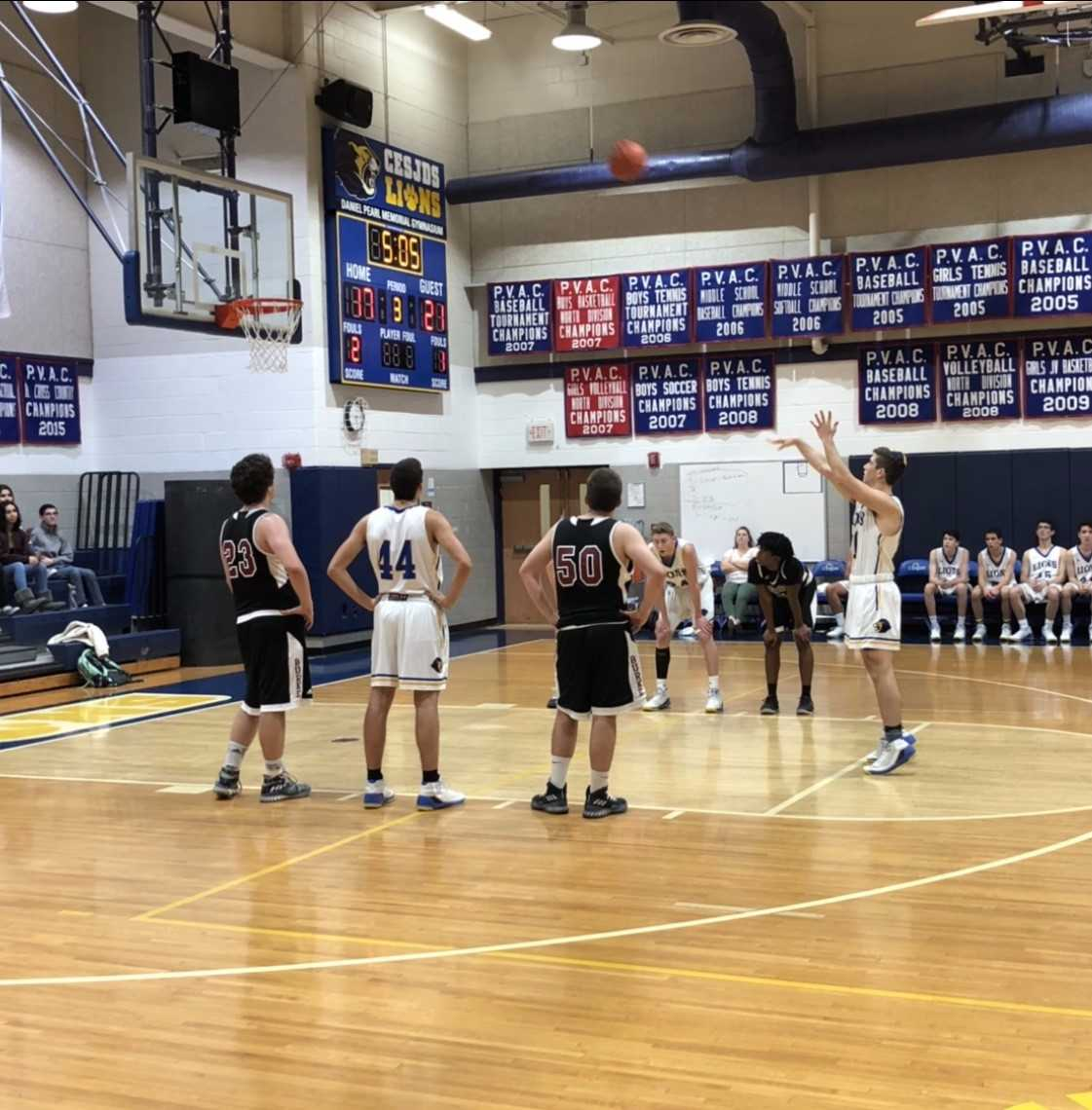 Junior Justin Galitzer holds his follow through as the ball soars toward the basket. The Lions outscored the Bengal Tigers during the third quarter.