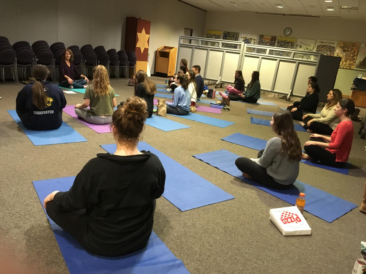 Students and faculty practice yoga poses in a yoga workshop during lunch and Community Time. It was the third part of the school's wellness series, which also included dog therapy and hypnosis sessions.