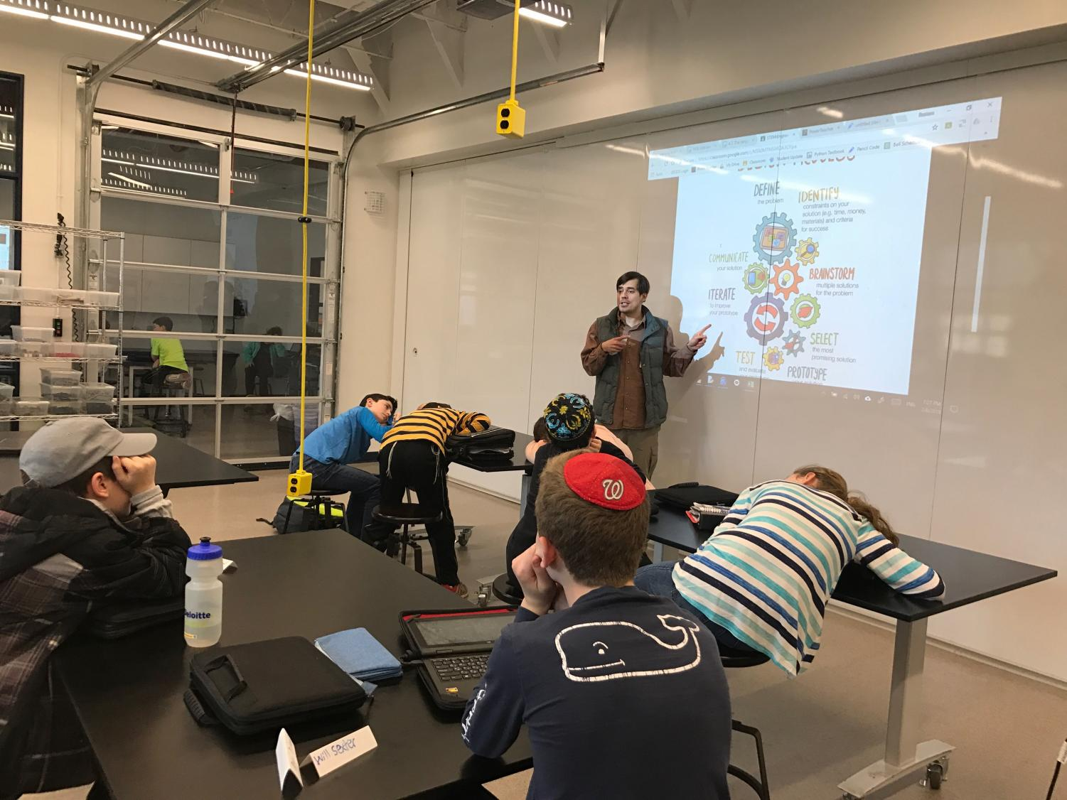 Meyer introduces a new project for middle school students who are taking coding this semester; the project involves following a list of procedures that are projected on the board.