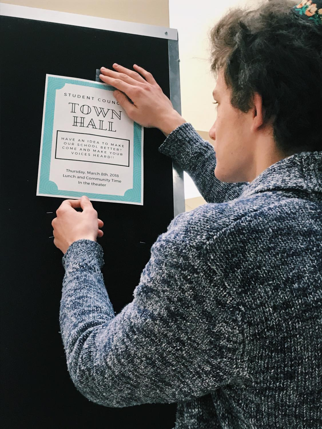 Sophomore class representative Matthew Wieseltier hangs town hall fliers to promote the event.