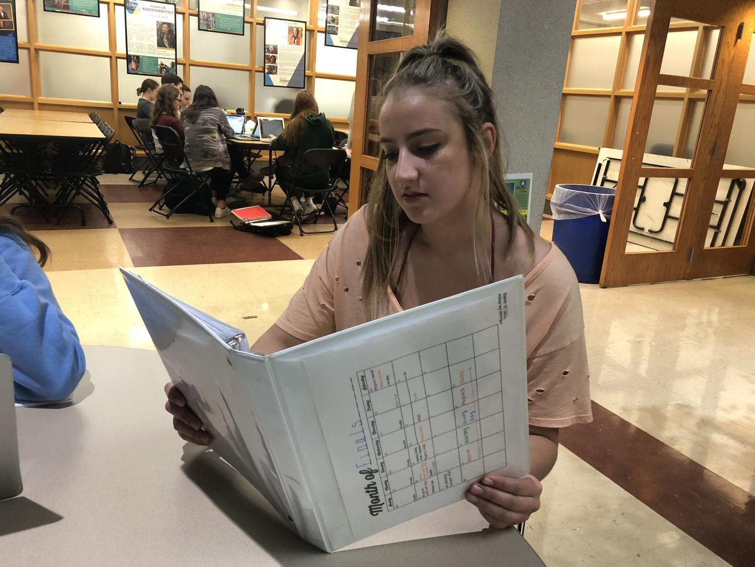 Junior Natalie Buckwold starts preparing for this year's final exams using a review binder. This year's final exams will count for less than previously.