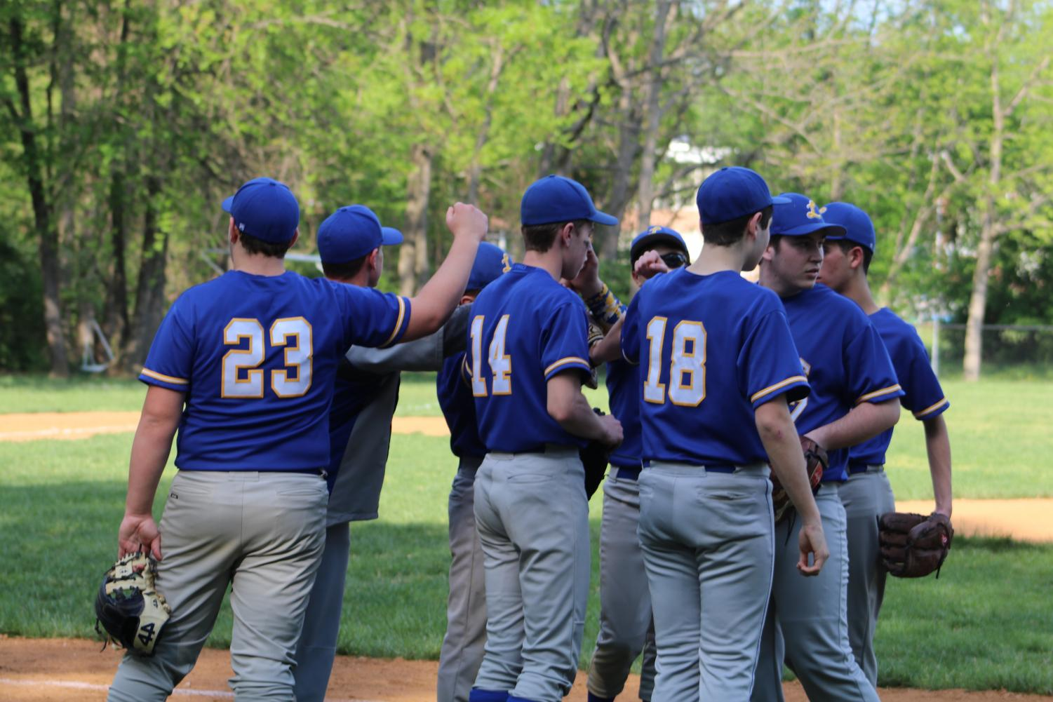 The baseball team gathers during a time-out during a game.