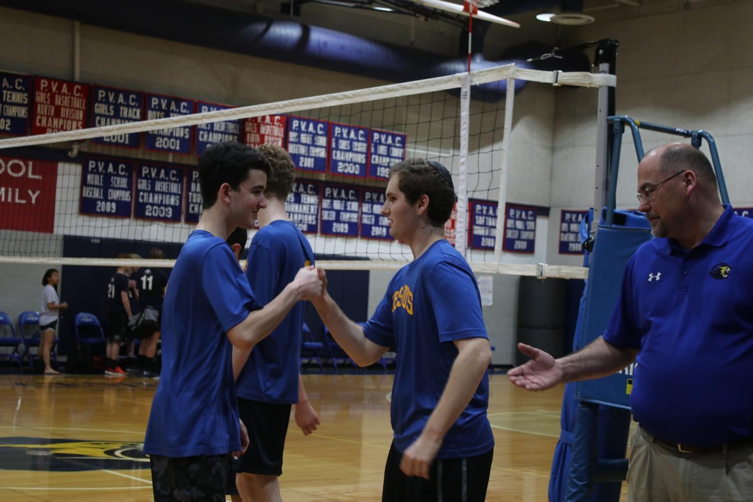 Science teacher and boys varsity volleyball coach Ray Hodges congratulates players following their junior night win against Trinity.  Hodges is one of eleven teachers who coached a school sports team this year.