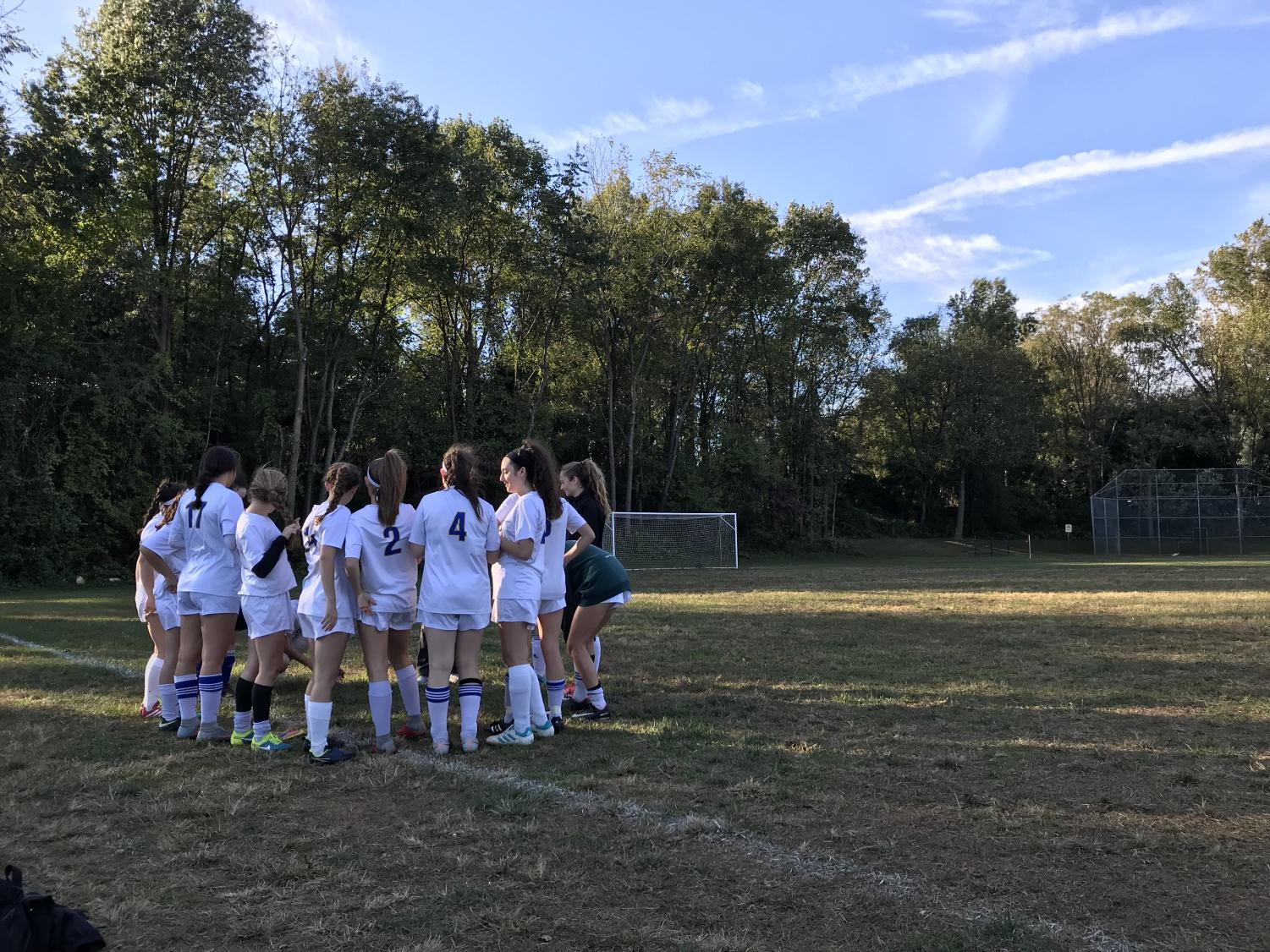 Girl's varsity Soccer gathers to discuss strategies, prior to the game.