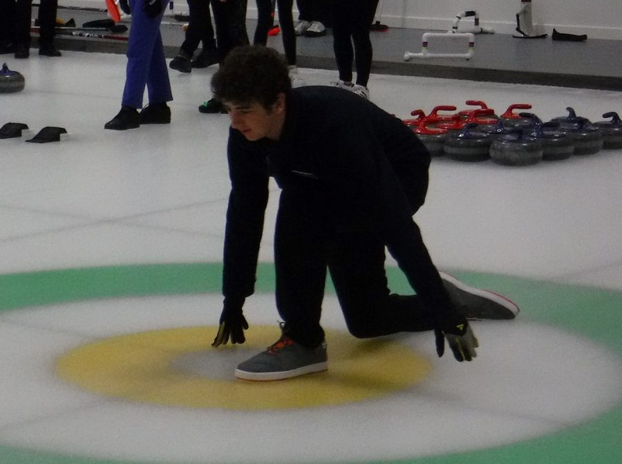 Sophomore Matan Rosenberg leads the Potomac Curling Club team by helping to strategize where to throw rocks in the arena.