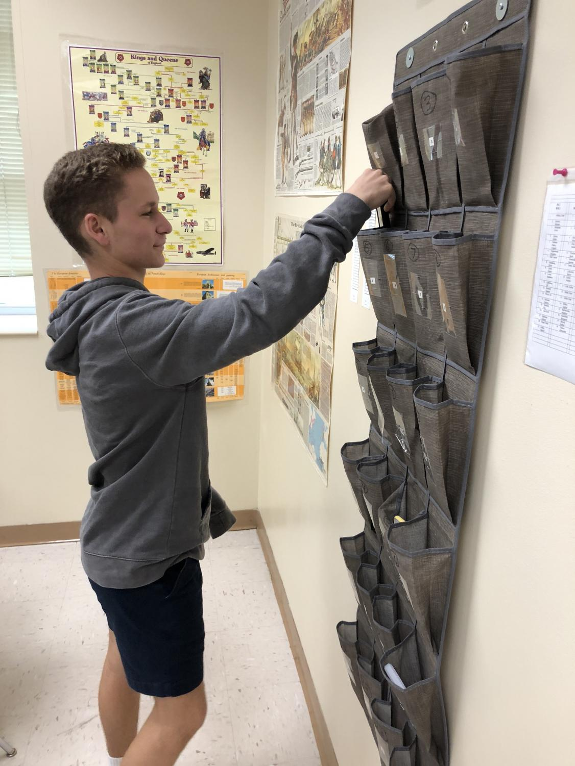 Sophomore Adam Alter places his phone in a container in a classroom. A phone holder is located in every classroom.