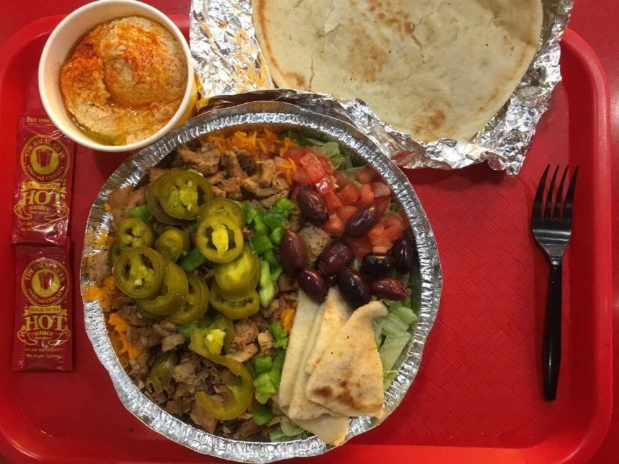 "The Halal Guys offers heaping rice platters with toppings of chicken, beef ""gyro,"" olives, lettuce and peppers on its menu."