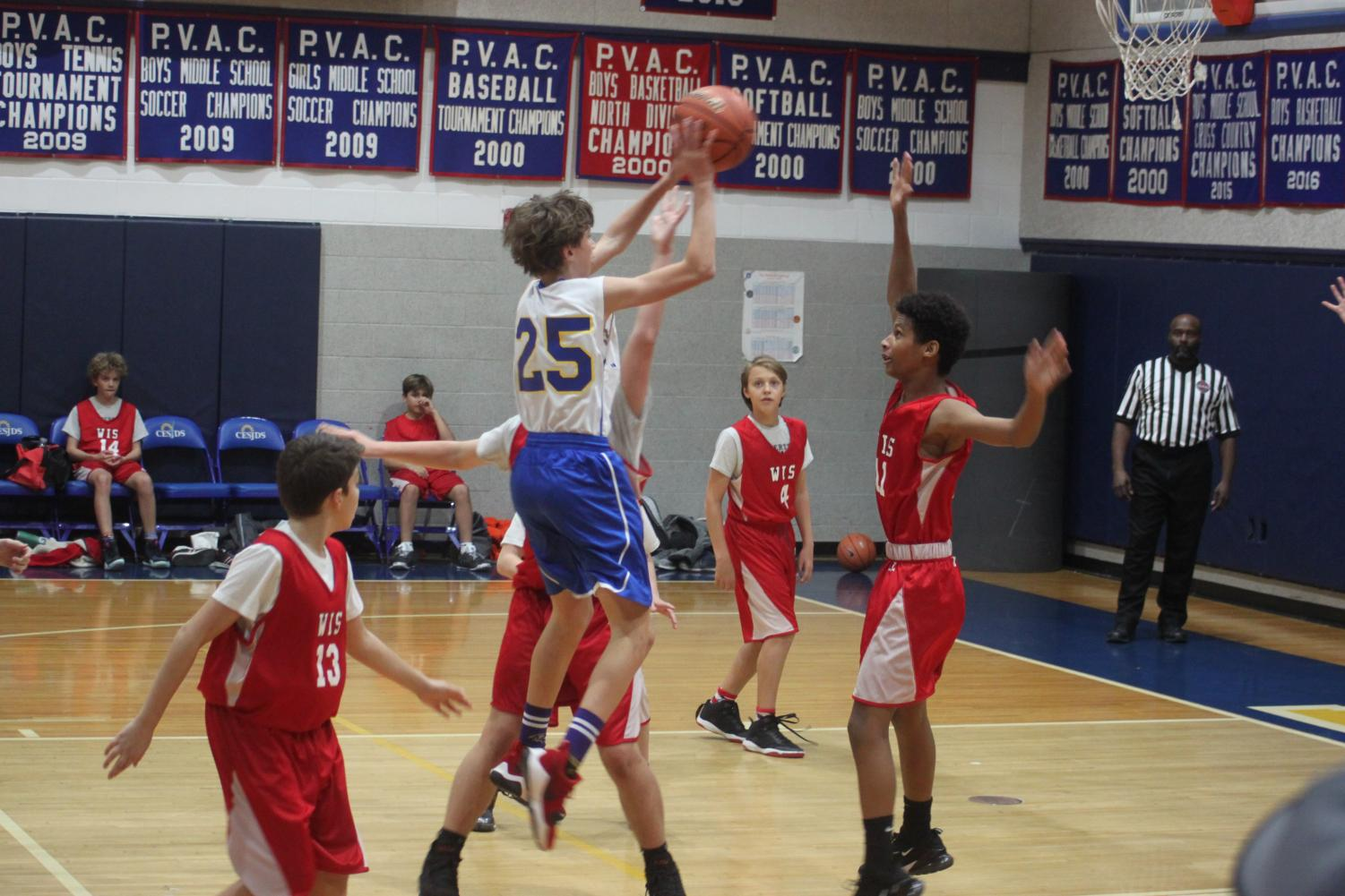 CESJDS eighth-grader and team co-captain David Fritz faces off against two WIS defenders making a jump shot.
