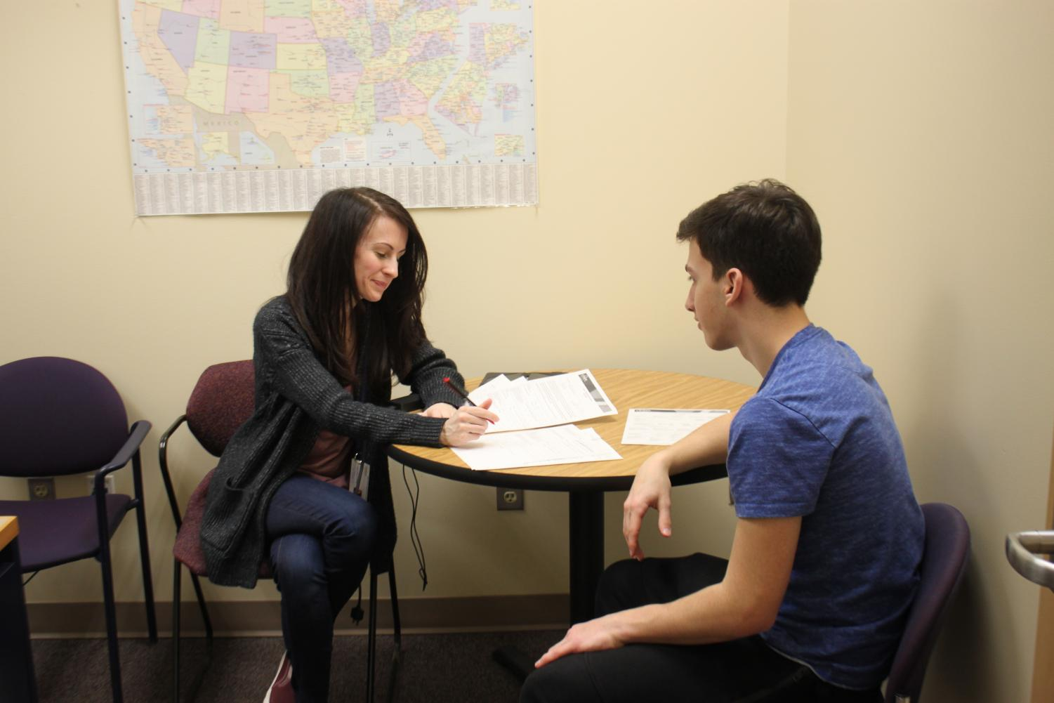 English teacher and college counselor Alison Davison sits down with a student to discuss his course requirements for graduating.