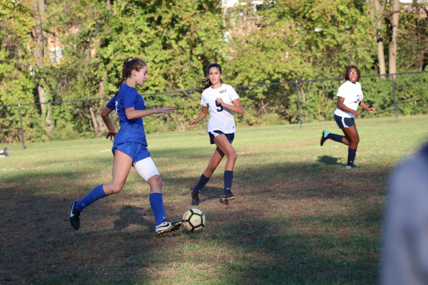 Junior Ally Knapp dribbles the ball around her opponent in a game.