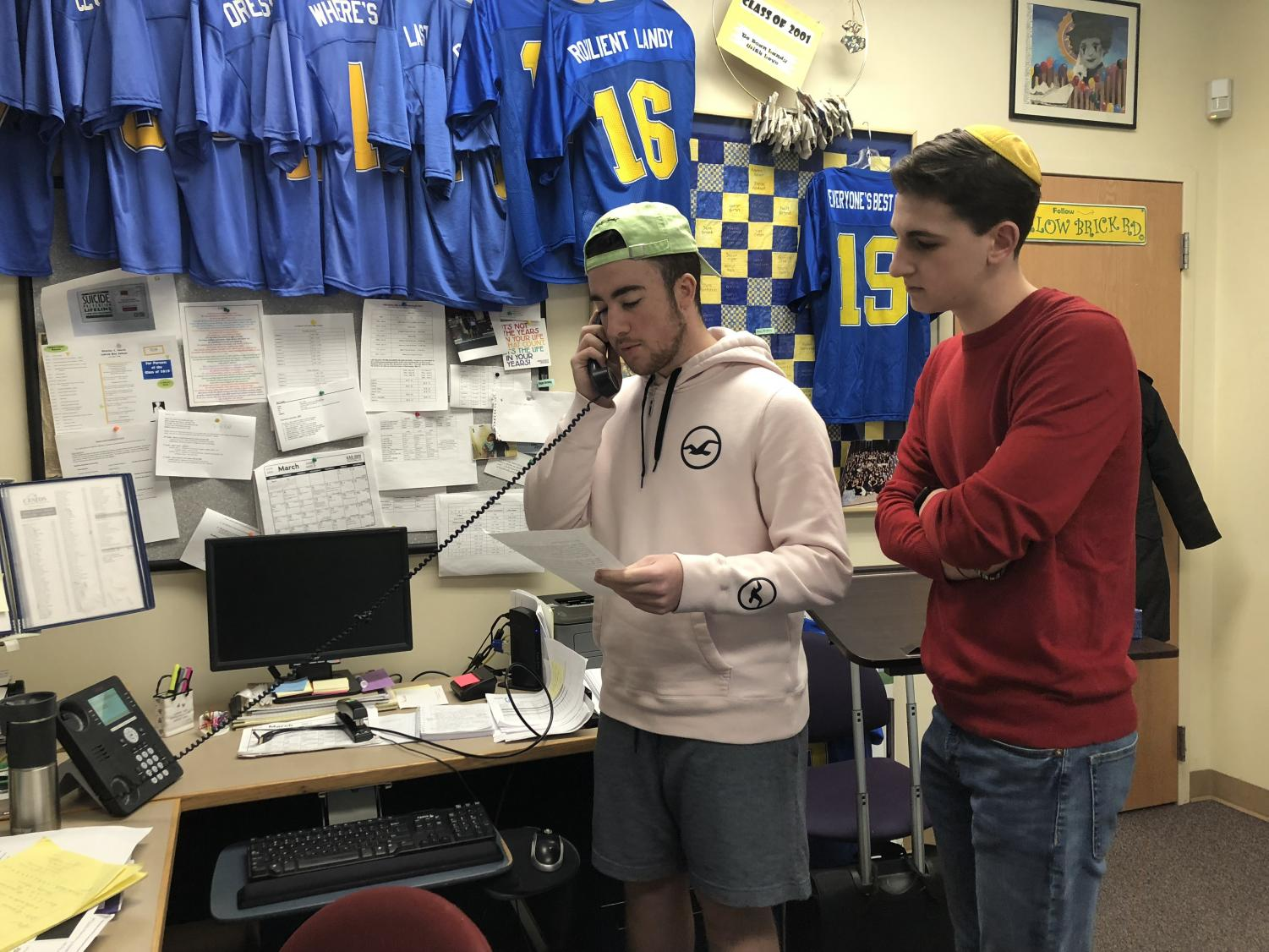 Junior Ryan Bauman and sophomore Alex Landy address the school over the PA system to commemorate the victims of the Parkland shooting and recent gun violence in America.