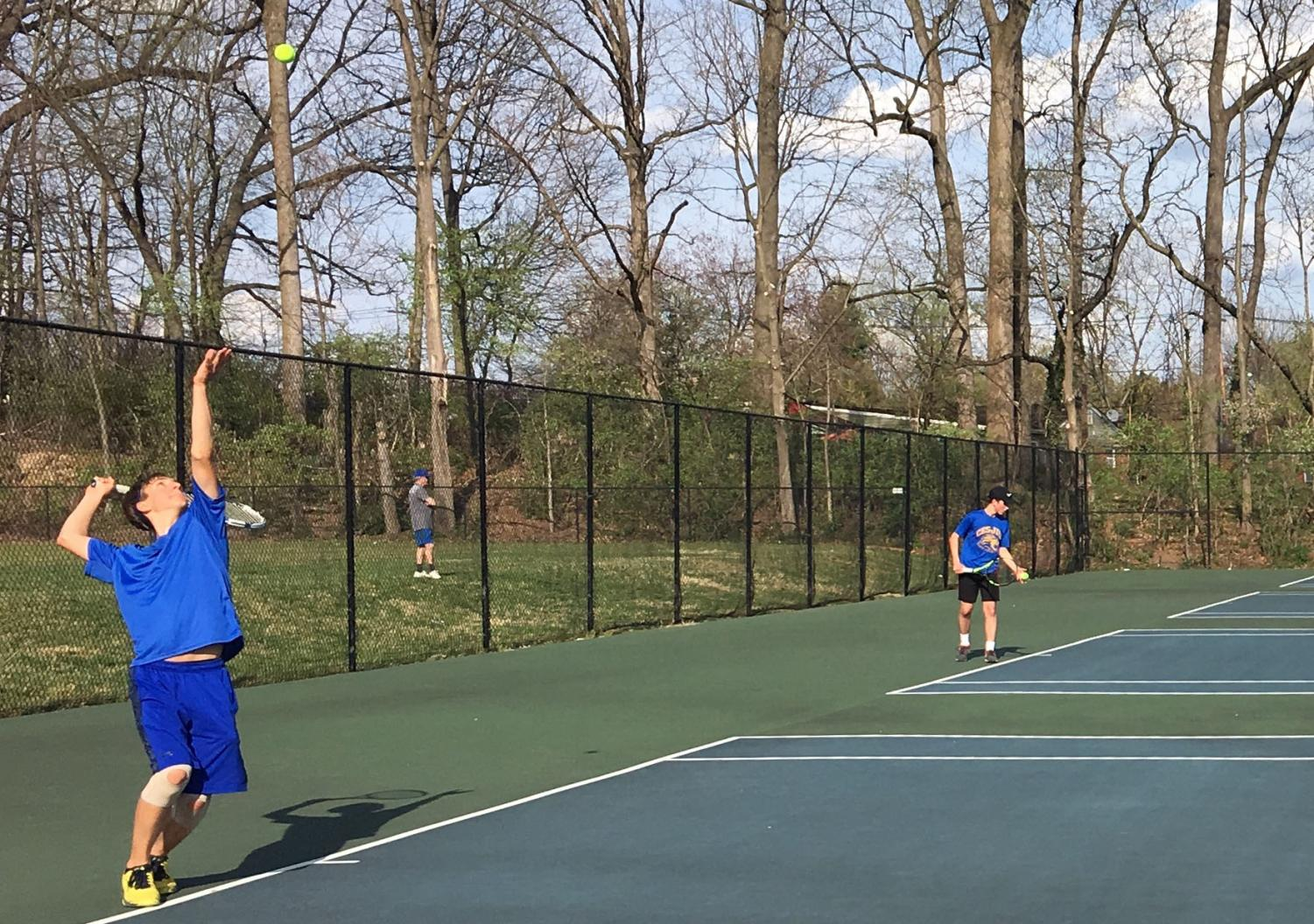 Junior and co-captain Matthew Lawrenz serves in the boys varsity tennis team's third game of the season.