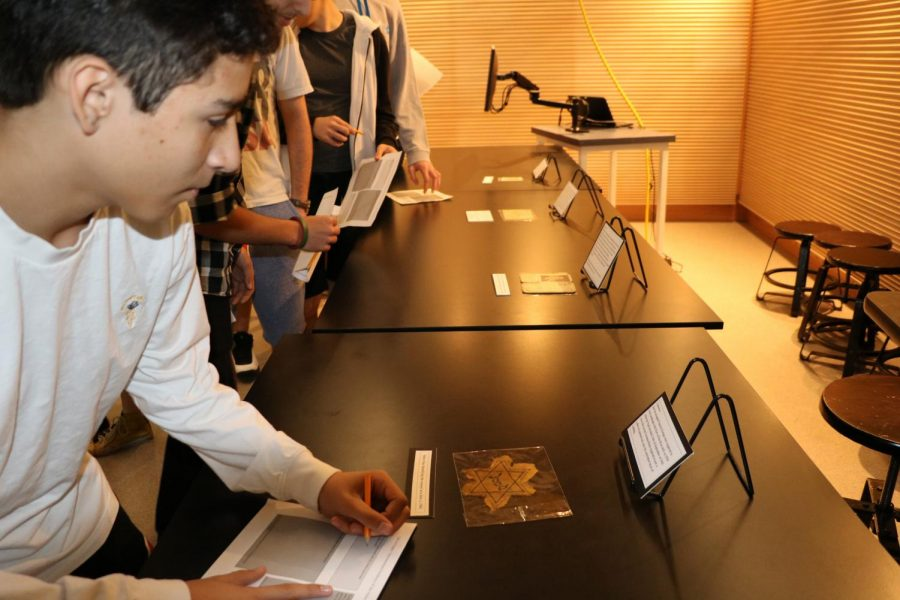 Sophomore Marshall Greenspan looks at Holocaust artifacts during second period on Yom HaShoah.