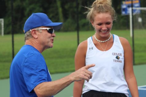 Mattingly gives feedback to singles player and junior Gigi Becker on her serve.