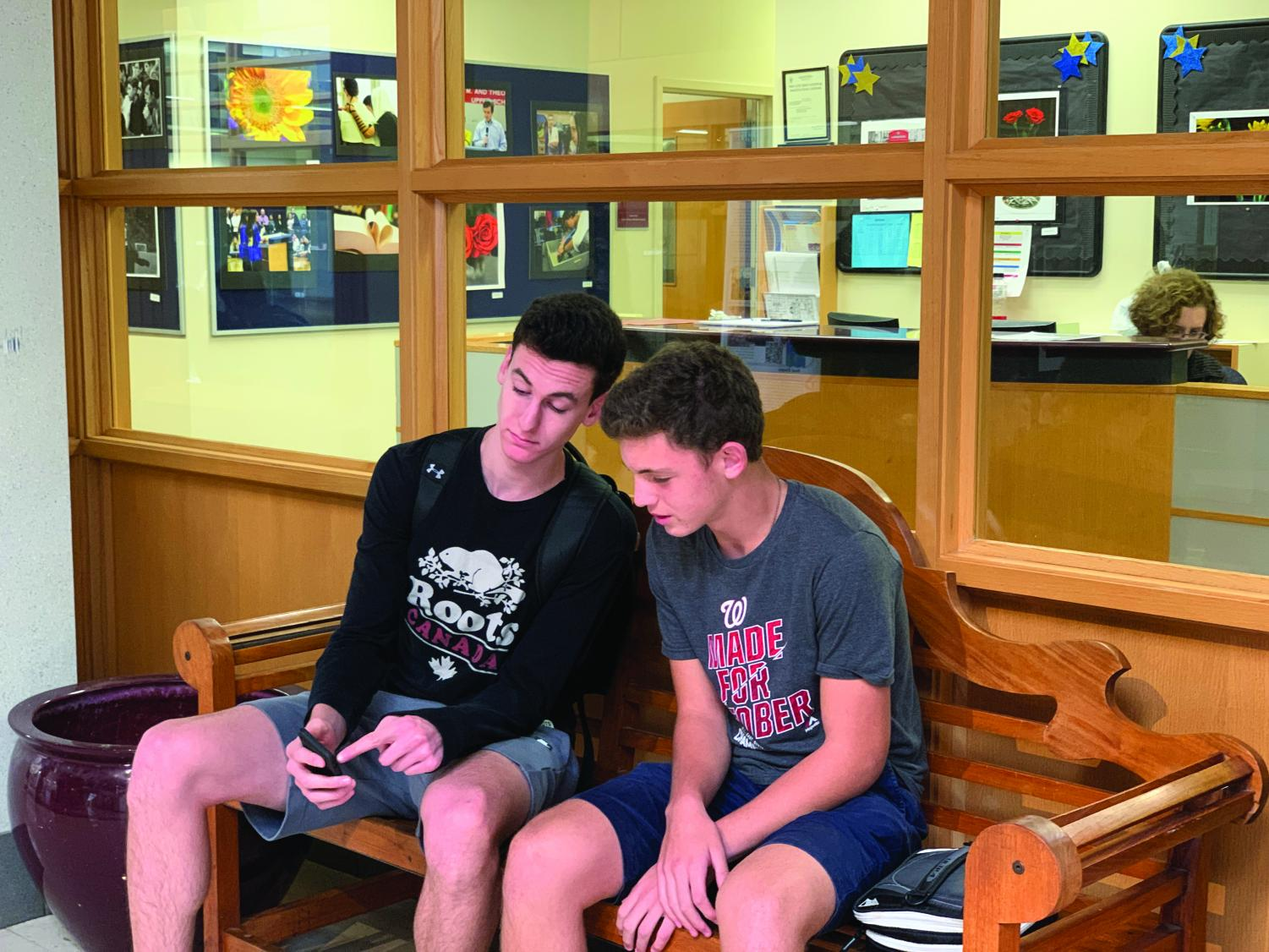 Junior Jacob Rulnick shows his admissions buddy, junior Alex Frame, a post on social media. Frame's previous school, the American Hebrew Academy, shut down over the summer, forcing him to quickly apply to a new school. Admissions  buddies  help ease the transition for new students by helping them with schedules, navigation and integration into their grade.