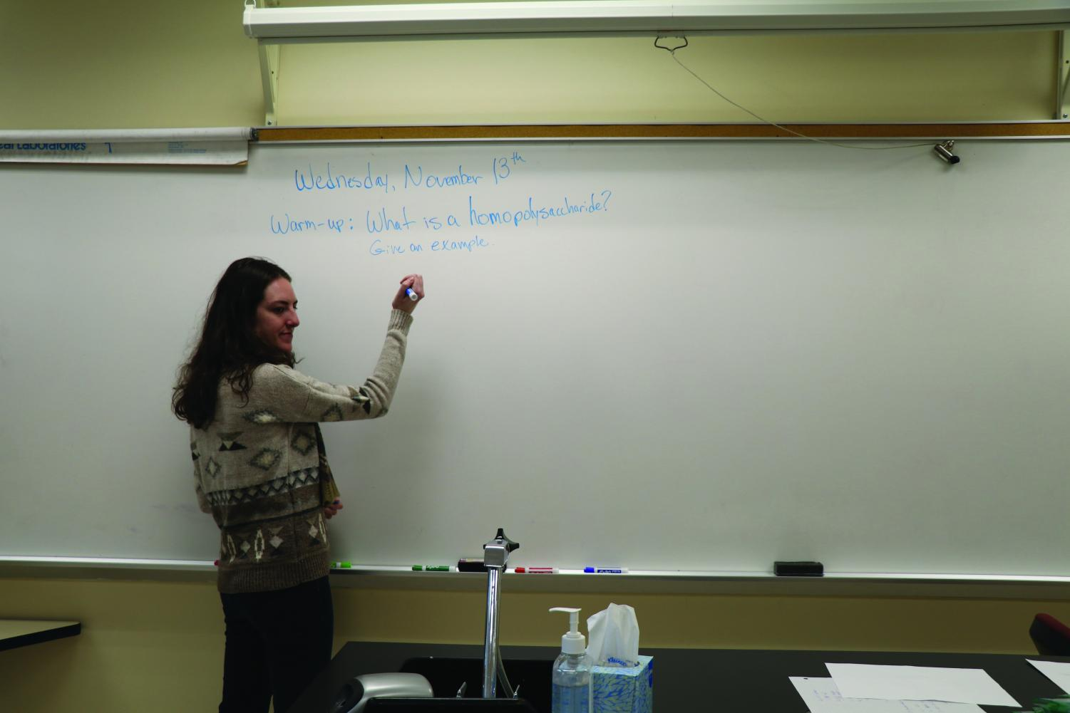Science teacher Emma Lucore writes down a science warm up for her ninth grade students. Lucore teaches biology.