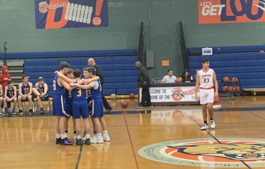 Boys junior varsity basketball players huddle at their season opener against rival Berman.