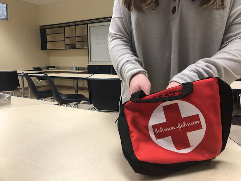 A student opens a standard first-aid kit in a classroom. New Stop the Bleed kits could change how JDS addresses medical emergencies on campus, most especially ones involving excessive blood loss.