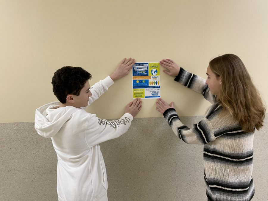 Eighth grade students Alec Silberg and Darya Dayanim place a poster for their capstone project on a wall.