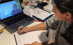 Junior Shevi Lerner takes notes while watching a video on her computer.