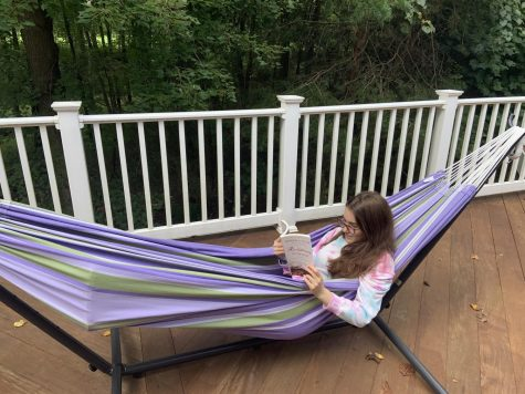 Junior Mira Beinart reads her history summer reading book in a hammock.