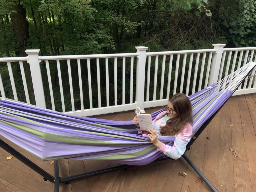 Junior+Mira+Beinart+reads+her+history+summer+reading+book+in+a+hammock.
