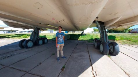Freshman David Skrynnikov stands at the landing gear of a supersonic aircraft located at the Oleg Antonov State Aviation Museum.