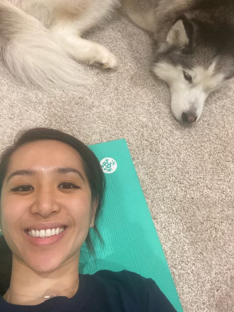Upper School STEM Coordinator Cassandra Batson takes a selfie with her dog while taking a break during a home yoga session.