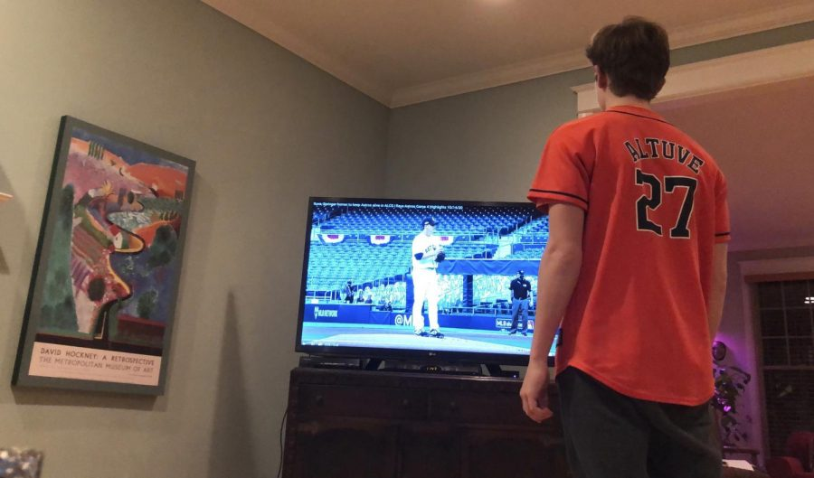 Sophomore Jonah Gross watches a baseball game from home with no fans in the crowd.
