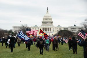 Rioters with flags march toward the Capitol Building early afternoon on Jan. 6.