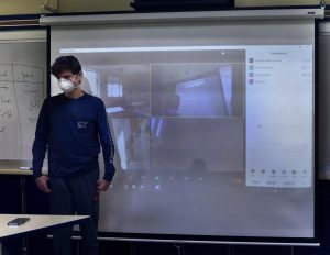 Freshman Todd Lazoff stands at the front a classroom with many of his peers participating through Zoom.