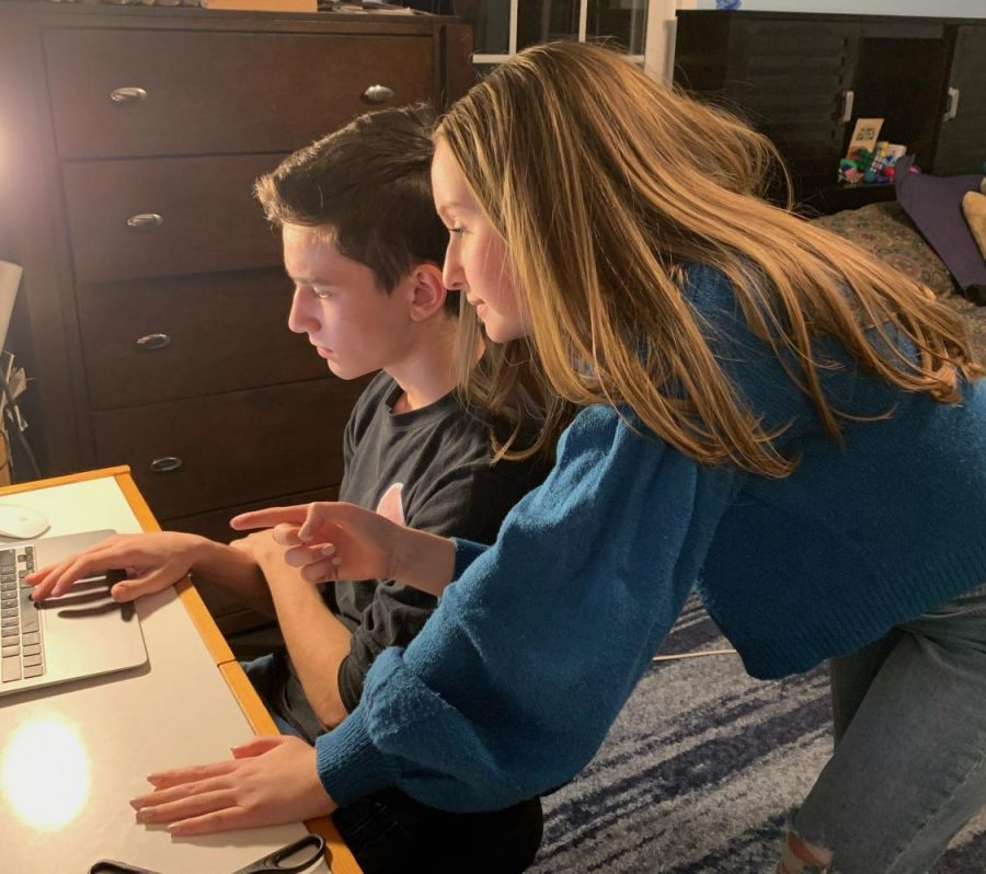 Junior Naomi Gould helps her brother, Freshman Jonathan Gould, with distance learning.