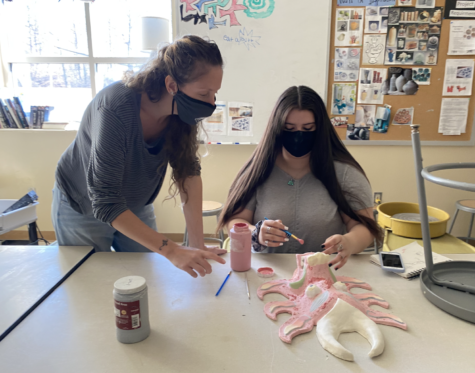 Ceramics teacher Gretchen Gobin helps student glaze their work.