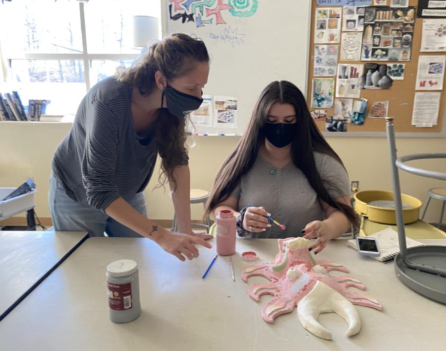 Ceramics teacher Gretchen Gobin helps student glaze their work.