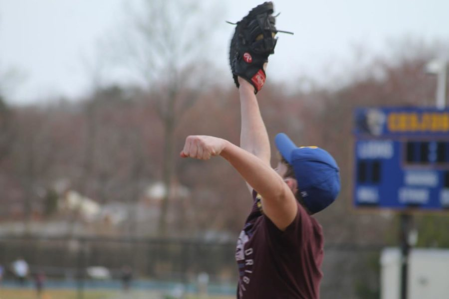 Sophomore Elliot Bramson fully extends his arm and catches the baseball with his glove. Throughout practice, Bramson played at first base and was able to catch anything that was in his area, no matter how far he had to reach.