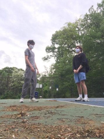 Fully vaccinated juniors Lincoln Aftergood and Sean Rich play together on the tennis courts with masks, despite new CDC guidelines.