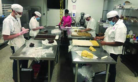Employees concentrate on baking an assortment of goods for their customers.