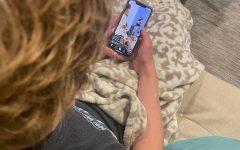 Junior Coby Malkus watching the viral TikTok posted by creator Lauren Zarras.